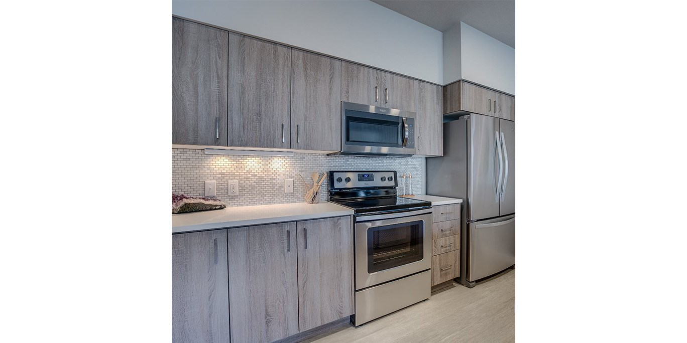 Tigard OR Apartments for Rent-Sygnii Updated Kitchen with Stylish Tile Backsplash and Matching Stainless Steel Appliances