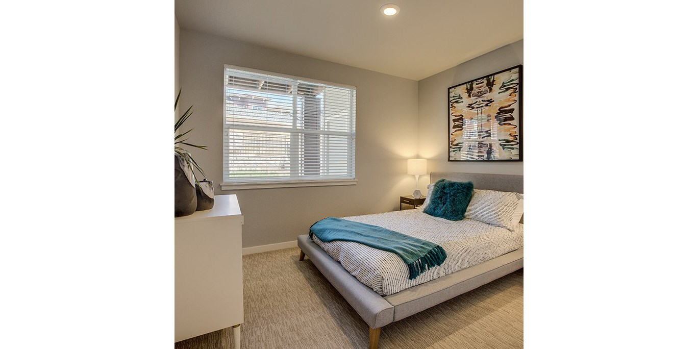 bedroom with large windowLuxury One Bedroom Apartments in Tigard OR-Sygnii Bedroom with Wall to Wall Carpet and a Large Window Letting In Natural Light