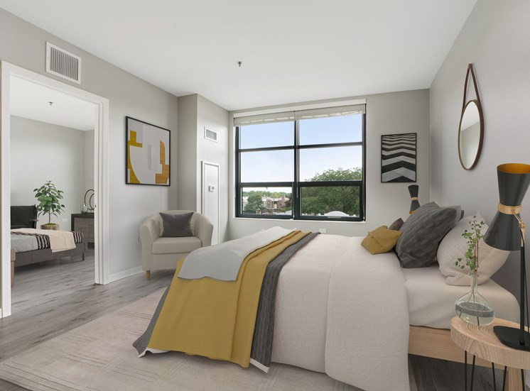 Bedroom with view, yellow and grey bedding, with a spacious layout, and view into another room.