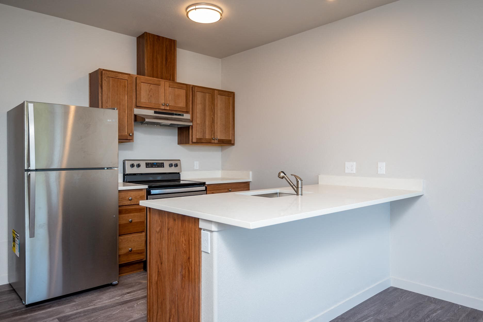 Galley style kitchen with white countertops, stainless steel refrigerator, stove, and hood vent. Brown cabinetry.