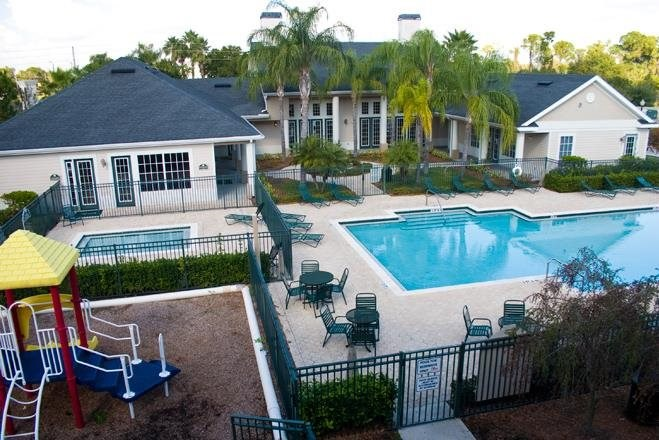 Aerial View of Leasing Office Exterior with Fenced in Swimming Pool and Sun Deck with Lounge Chairs with Trees Wading Pool and Playground in the Background