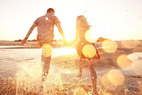 Couple holding hands walking away in the water