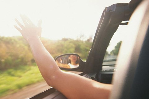 Woman driving at sunset waving her arm out of the car