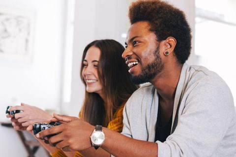 Couple smiling holding controllers while playing video games