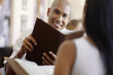 Couple eating at a restaurant smiling and holding menus