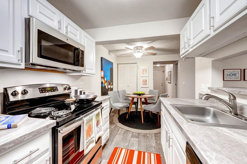 Kitchen with White cabinetry, light grey countertops and appliances including dishwasher, stove, oven and microwave