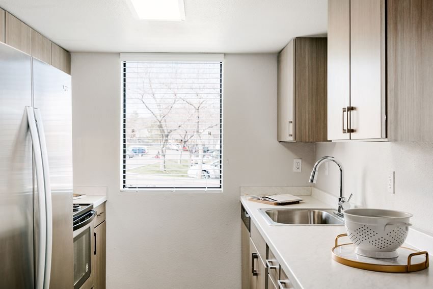 Renovated kitchen with light brown cabinetry and stainless steel appliances