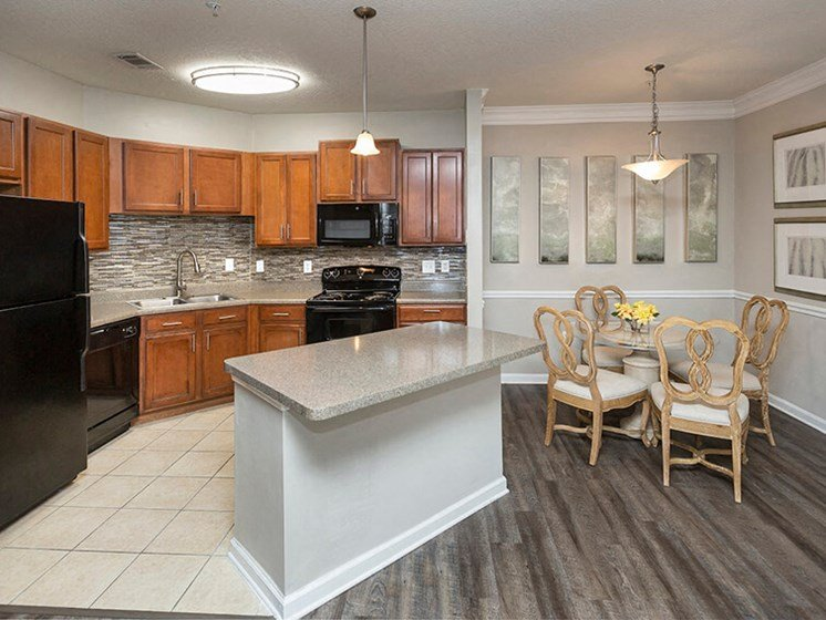 Open Floor Plan Kitchen with Wood Plank Vinyl Flooring (in Select Units) and Maple Raised-Panel Cabinetry at Reserve Bartram Springs, Jacksonville, FL, 32258