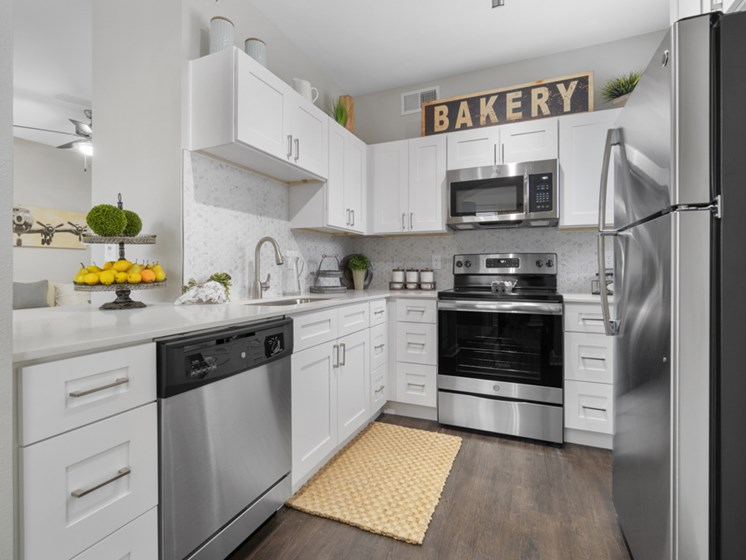 The Colony Apartments for Rent-Flatiron District at Austin Ranch Kitchen with Matching Stainless Steel Appliances, Stylish-TIle Backsplash, and White Cabinets
