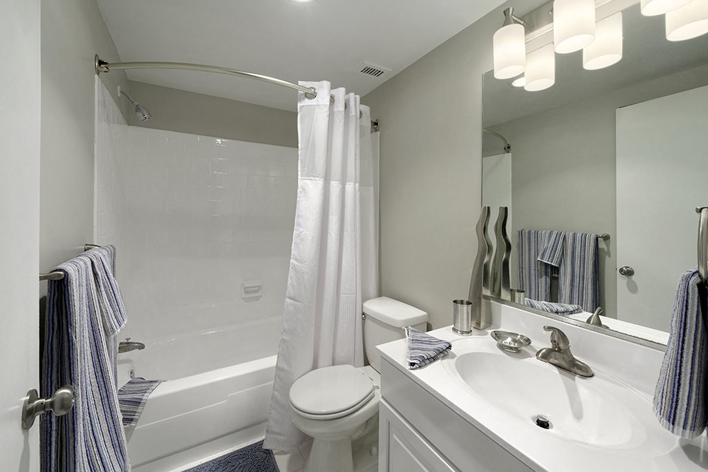 Clean white bathrooms with a tub at Circle Towers in Fairfax, VA