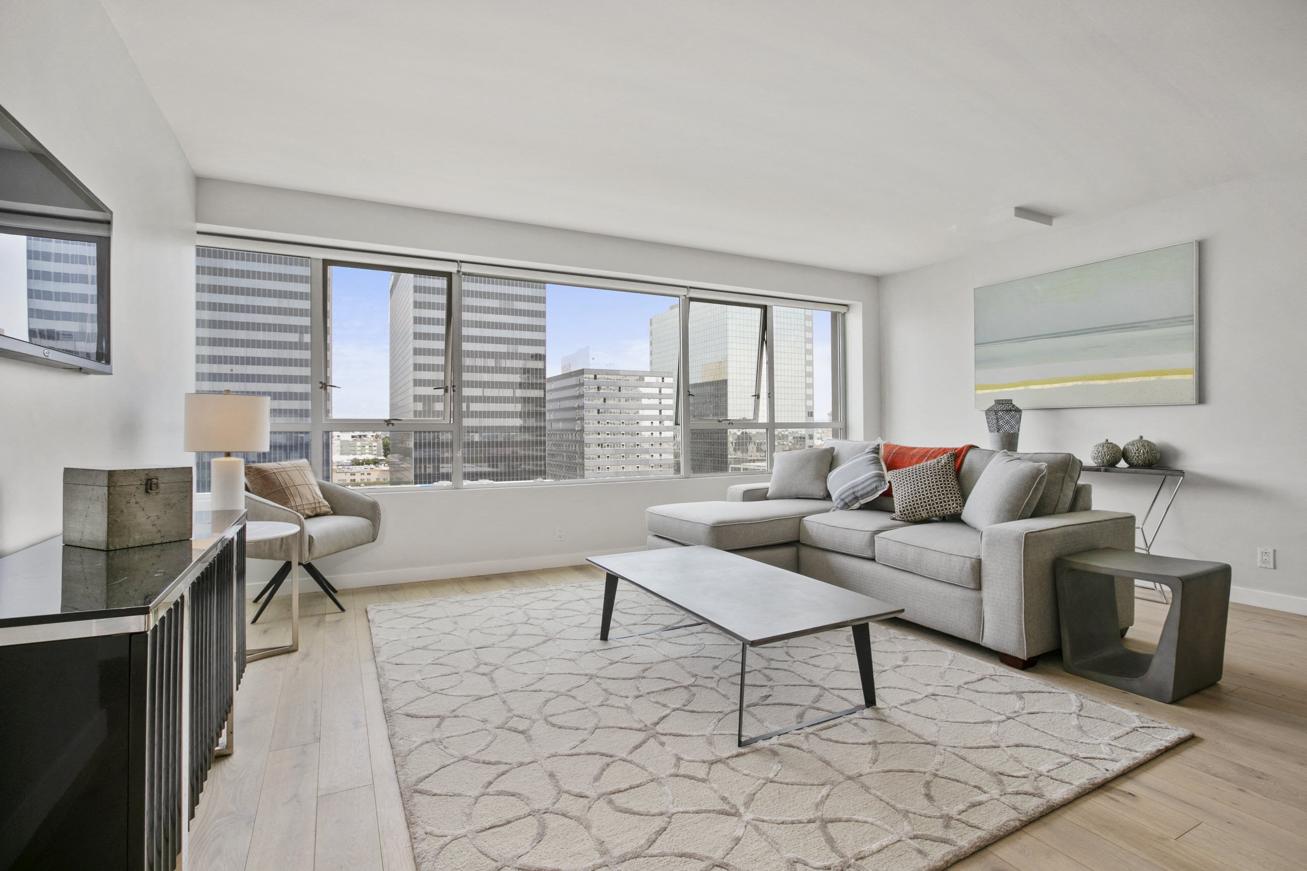 Apartments in Koreatown, CA - The View Apartments Living Room with Hardwood-Style Flooring and Large Windows Providing Skyline Views