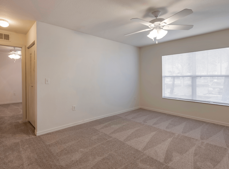 Carpeted Room with Window and Ceiling Fan