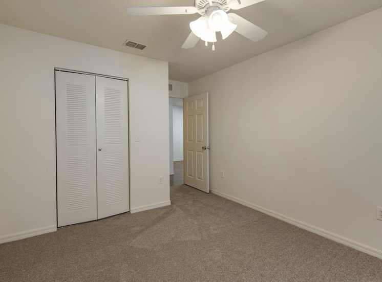 Carpeted Room with Folding Closet Door and Ceiling Fan