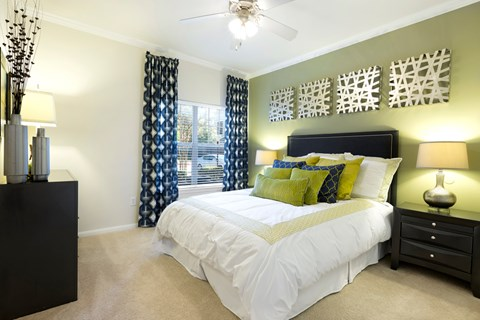 Bedroom with ceiling fan and plush carpet