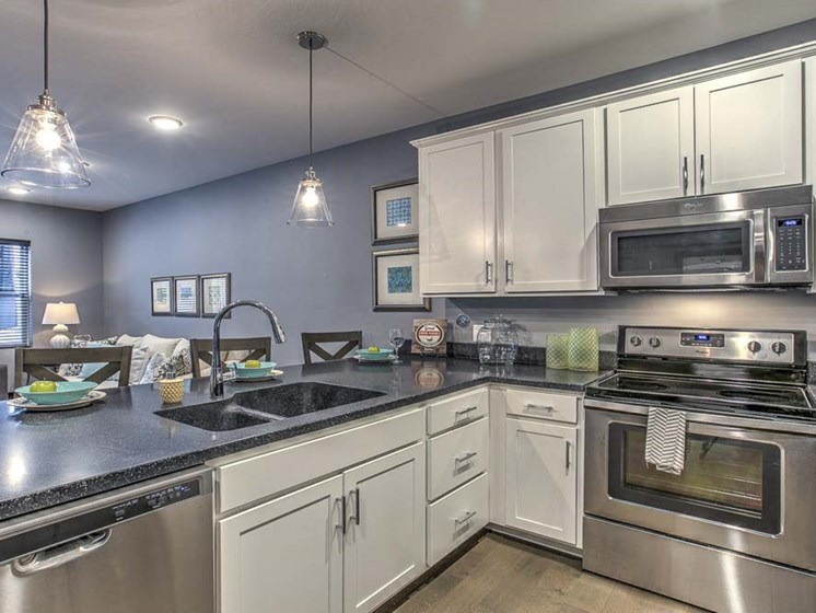 Large open floor plan kitchen with white cabinetry and stainless steel appliances