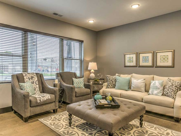 Furnished open floor plan living room with large windows for natural light at The Helen
