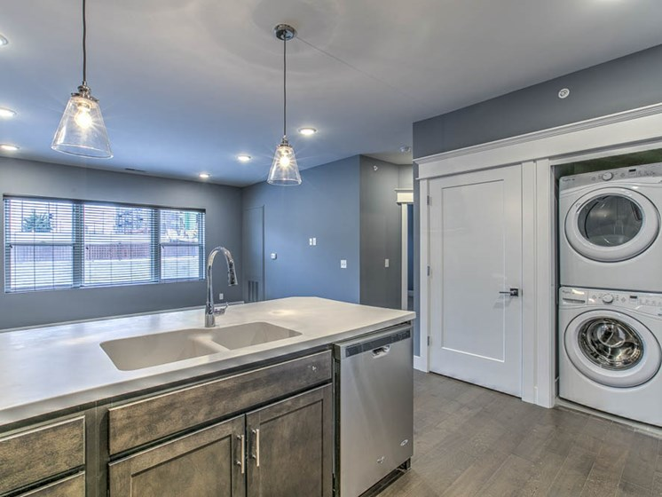 Kitchen with hanging light fixtures and washer and dryer in attached closet at The Helen