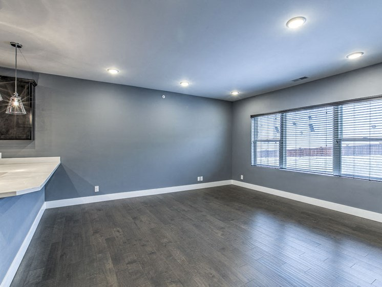 Large living space with hardwood-style flooring and large windows providing natural light at The Helen