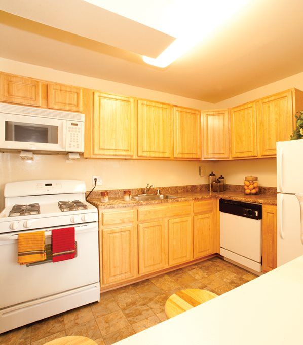 kitchen at Cheverly Station apartmentst with white appliances and light wood grain cabinets
