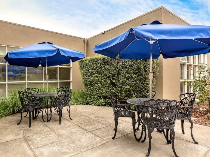 Umbrella Patio Lounge with Stunning Views at Pacifica Senior Living Mission Villa, Daly City