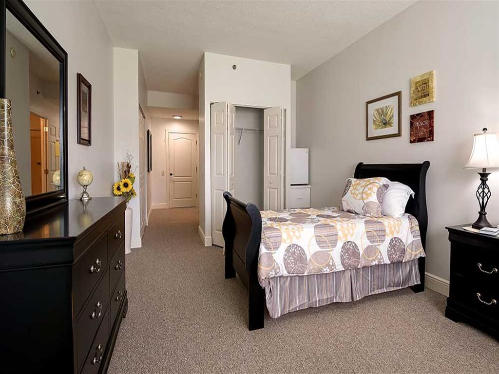 Traditional decorated with views and wood furniture bedroom at Pacifica Senior Living Ocala