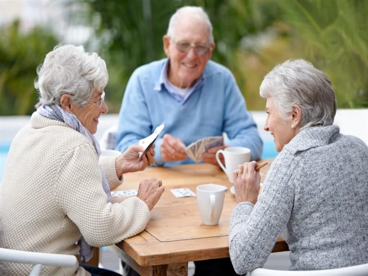 Seniors having a cup of coffee and playing cards at Pacifica Senior Living Vista in Vista, California