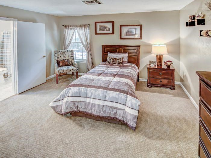 Bedroom with comfortable bed in Pacifica Senior Living Woodmont