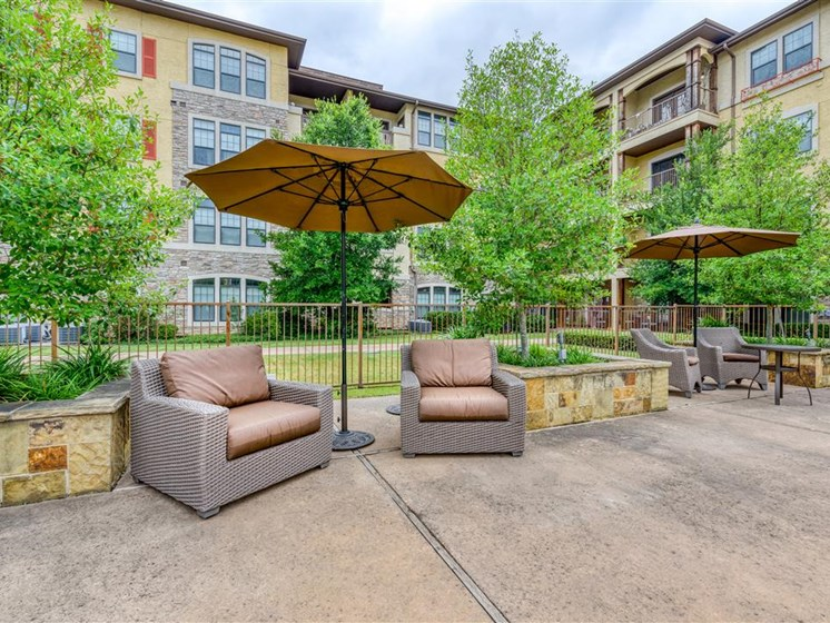 Poolside chairs and umbrella at The Meridian at Kessler Park