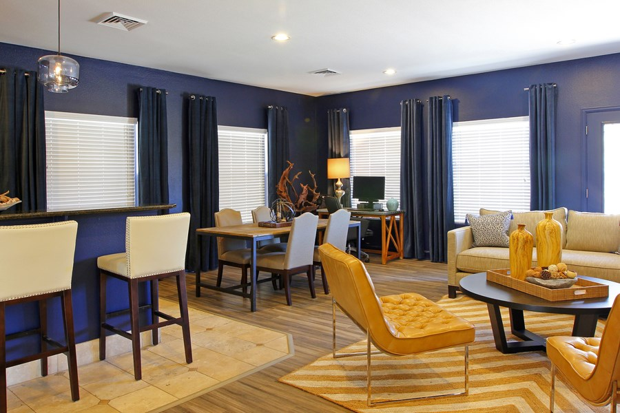 Ardenne Apartments Clubhouse with navy walls, large windows and beige and white chairs.