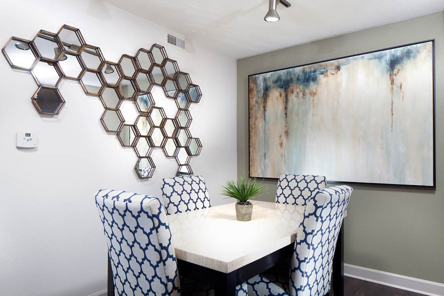 Ardenne Apartments Dining room with white table, blue and white chairs, grey walls and mirror art