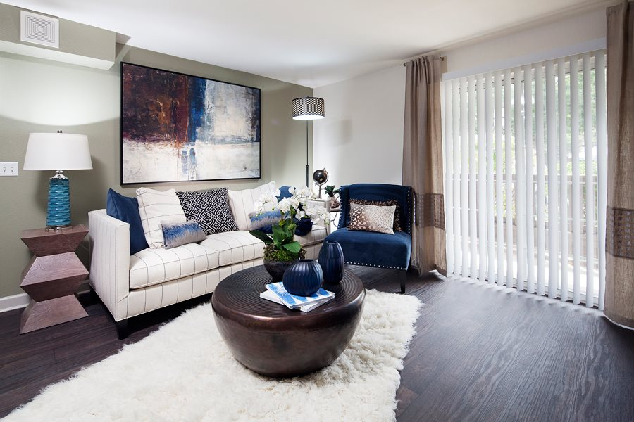 Ardenne Apartments model apartments with a white couch, blue chair and hardwood-style floor