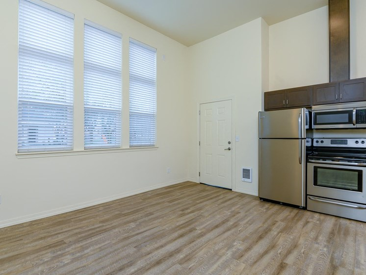 Kitchen open to living room with three large windows in living room.