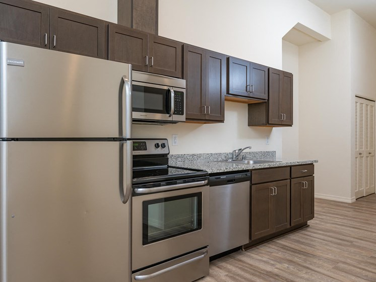 Midtown apartments kitchen. Dark cabinetry, stainless steel appliances including refrigerator, stove/oven, microwave and dishwasher.