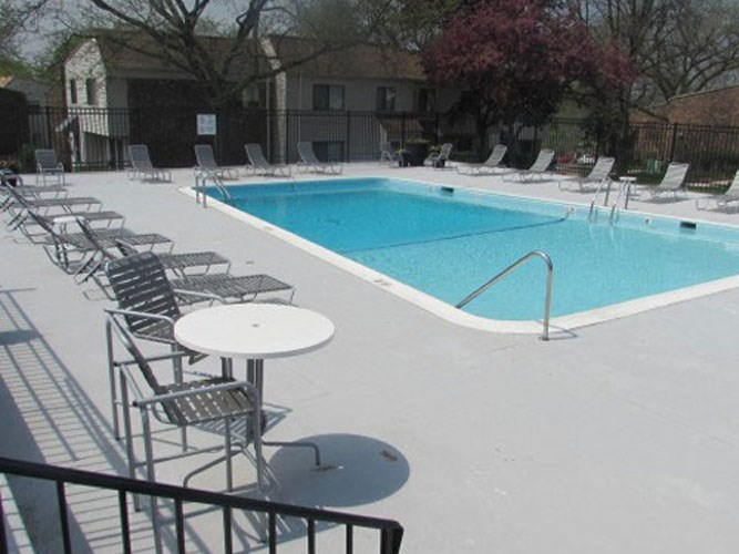 Outside pool with lounge chairs at The Townhomes at Highcrest in Woodridge, IL