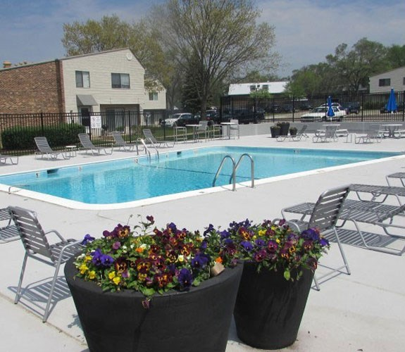 Outside pool with outdoor furniture with umbrellas at The Townhomes at Highcrest in Woodridge, IL