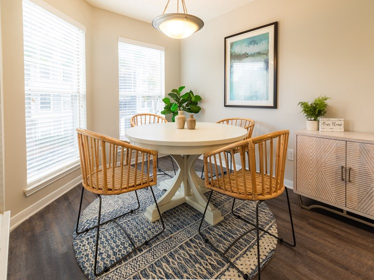 Renovated interiors featuring wood style flooring and modern fixtures in the dining room at Arbors Harbor Town Apartment Homes in Memphis, TN 38103