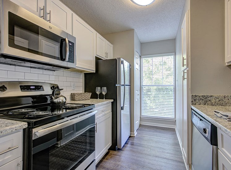 Newly Renovated Kitchens with White Subway Tile Backsplash and Sleek Black and Stainless Steel Appliances and Gorgeous Countertops at Arbors Harbor Town Apartment Homes, Memphis, TN 38103