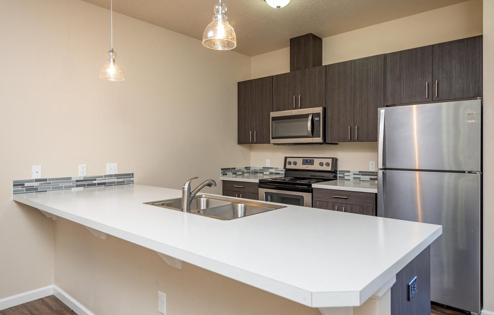 Claxter Park Apartments | Interior kitchen with white quartz countertops, stainless steel refrigerator, stove and upper microwave. Blue and grey backsplash tile. Dark lower and upper cabinetry.