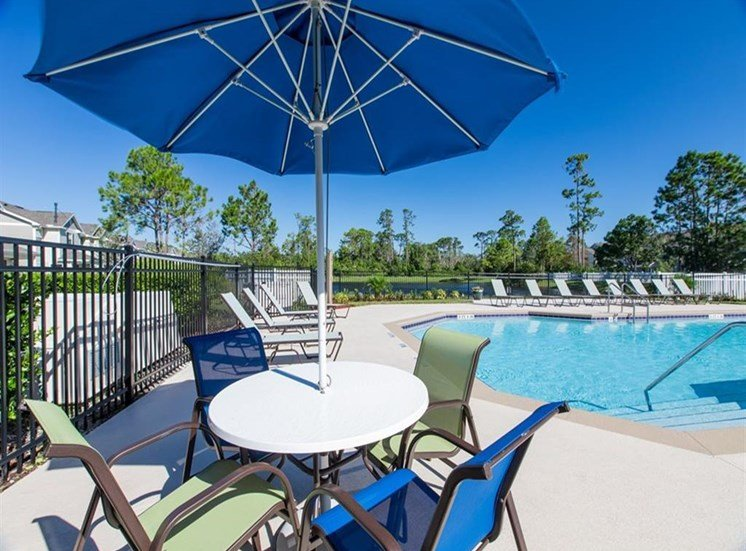 Large outdoor pool with umbrellas with patio furniture at Sunrise Point in Port Orange, FL