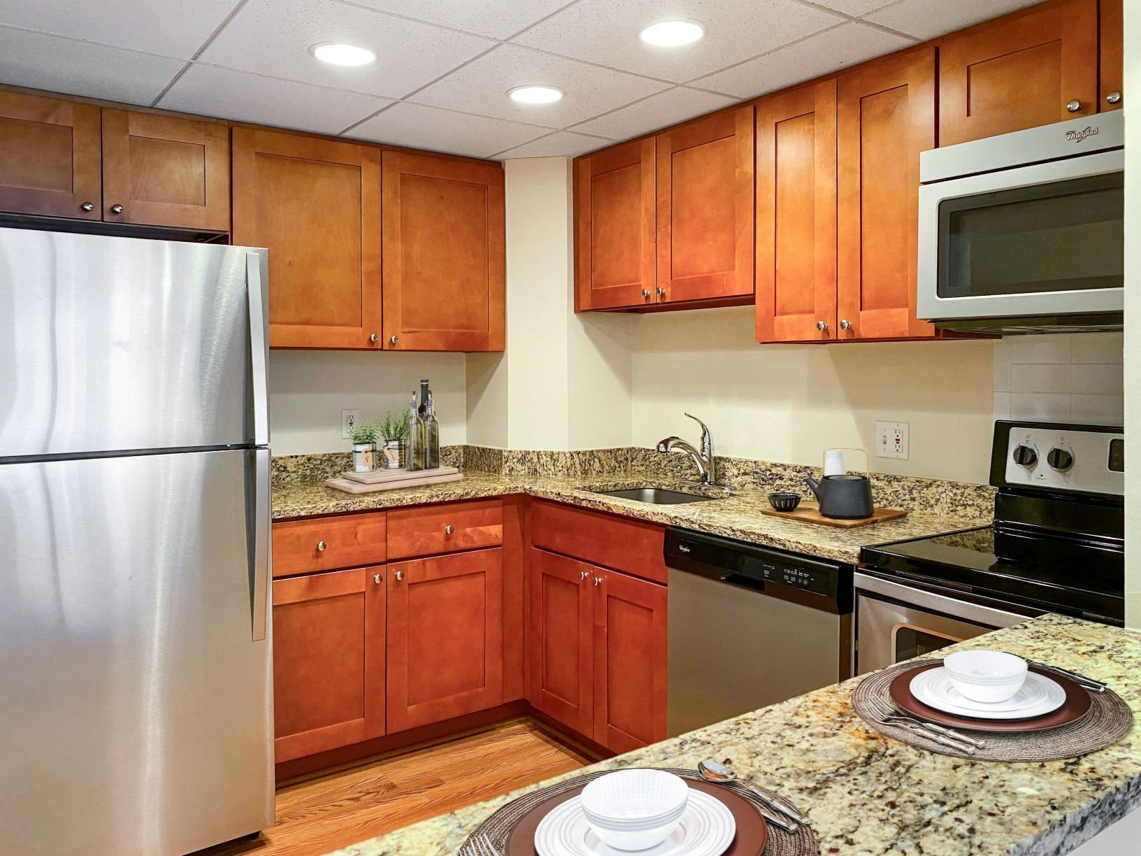 Renovated kitchen at Lenox Club in Crystal City with wood cabinets, granite countertops, stainless steel appliances