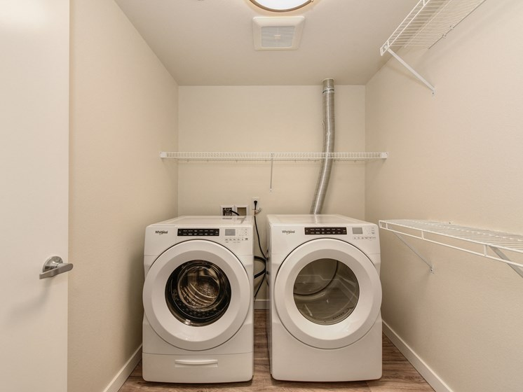 Singular Washer and Dryer Machine Room with White Walls and Shelves