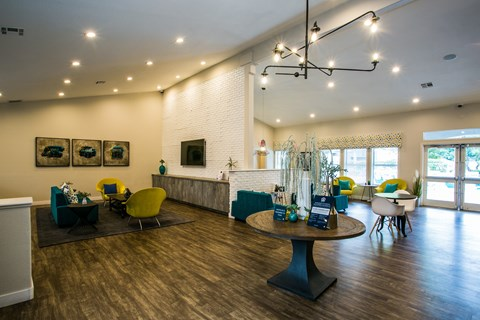 Clubhouse with lounge seating, tables and wall tv