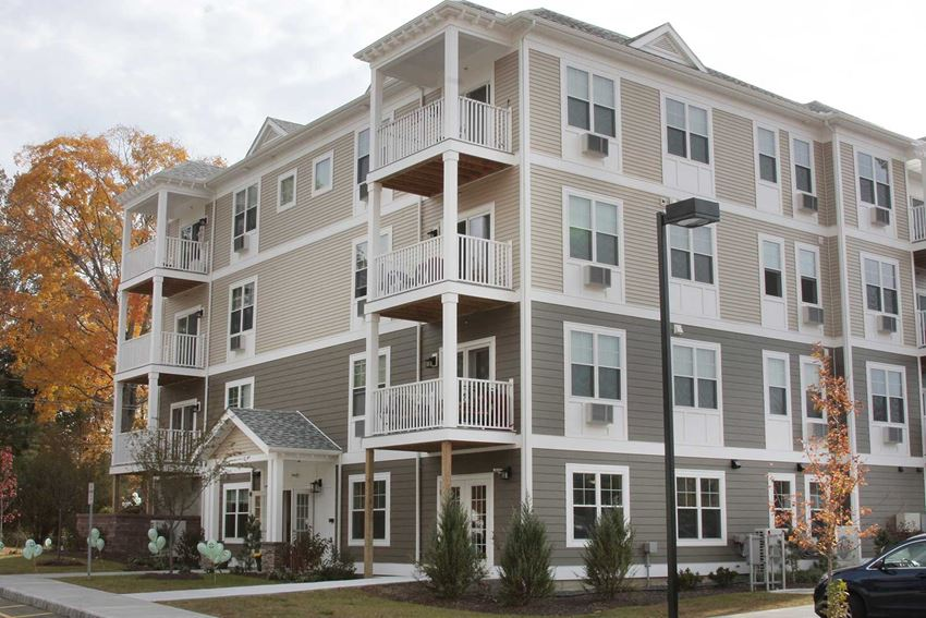 Laurel Hill Residences building exterior shows modern construction, lots of windows, professional landscaping, and balconies on floors 2-4.