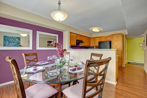 Apartment dining area with dining set and kitchen in background