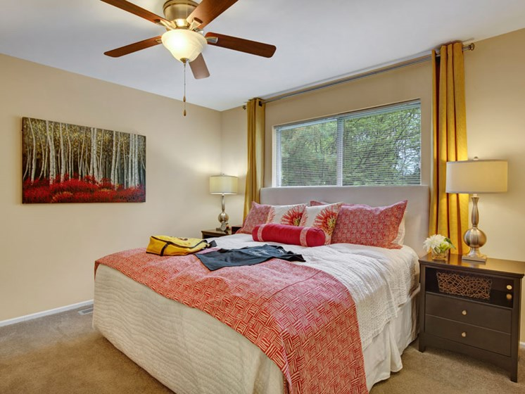 Furnished apartment bedroom with ceiling fan and large window