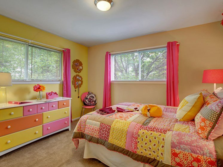 Furnished apartment bedroom with two large windows and colorful furniture
