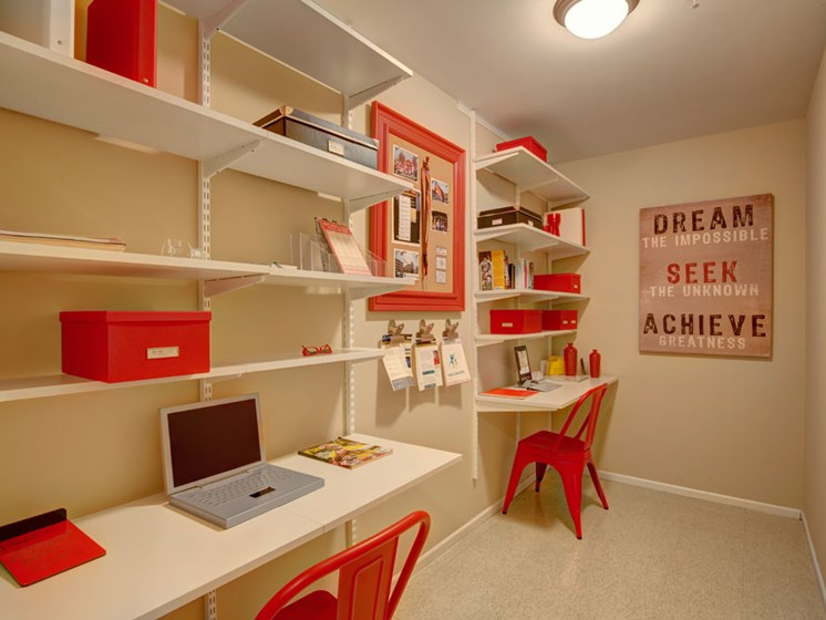 Large walk in closet set up as an office space with shelving and furnishings