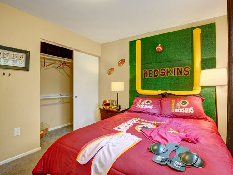 Furnished apartment bedroom with large closet and Redskins themed decor
