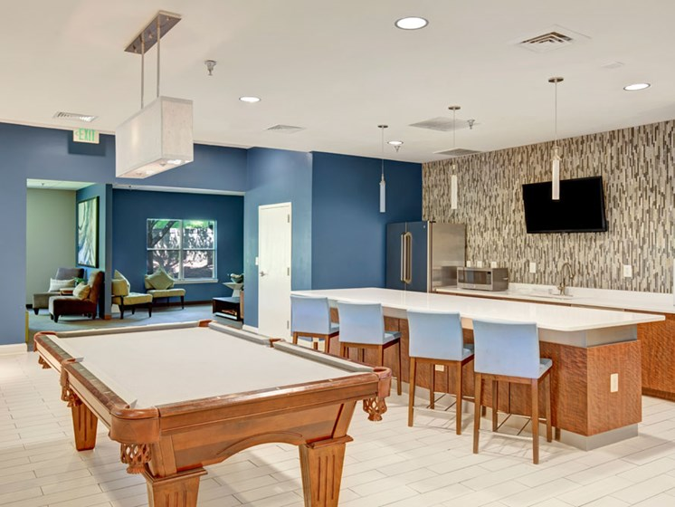 Clubhouse common area kitchen with bar seating and billiards pool table