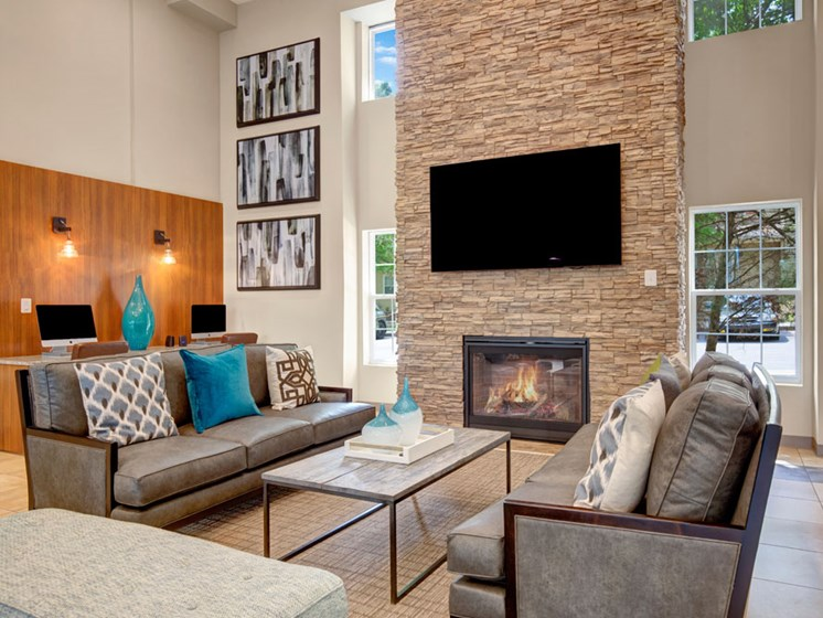 Clubhouse lounge with seating area and TV over fireplace
